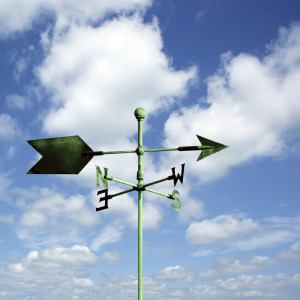 green copper wind vane with bright sky, square frame