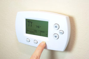 Female hand setting a digital thermostat